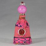 Small pink Genie bottle embellished with a beaded lid. The genie inside watches over a dangling key. Perhaps the key to your greatest wish?